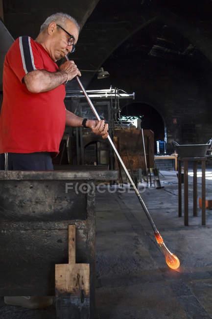 Человек дует с трубчатым расплавленным стеклом на стекольном заводе — стоковое фото