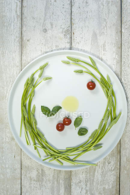 Wild asparagus on plate, olive oil, tomatoes and basil — Stock Photo