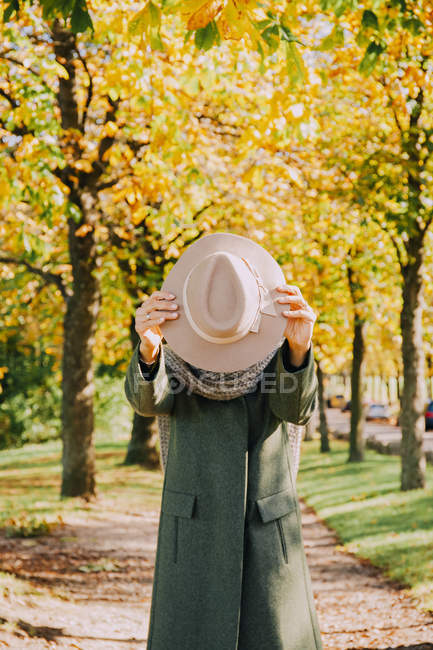 Woman hiding her face behind hat — Stock Photo