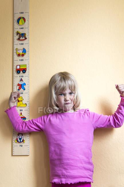 Little girl standing beside yardstick — Stock Photo
