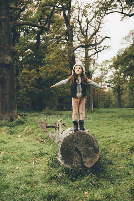 Kleine Mädchen tragen Kappe stehend mit ausgebreiteten Armen auf einem Baumstamm im herbstlichen park — Stockfoto