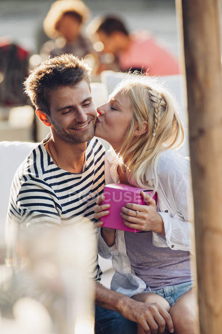 Donna baciare fidanzato al caffè all'aperto — Foto stock