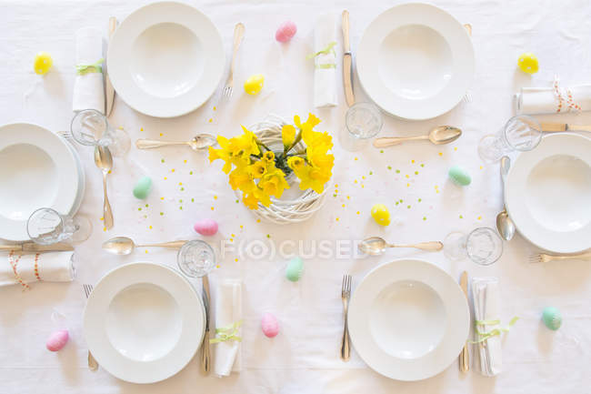 Laid Easter table decorated with bunch of daffodils — Stock Photo