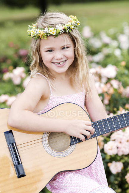 Girl with guitar wearing floral wreath — Stock Photo