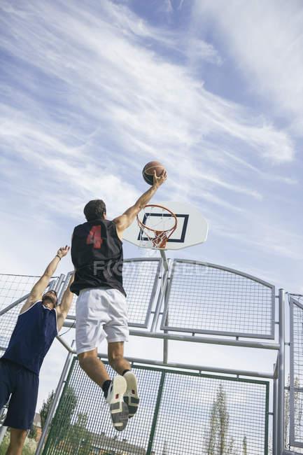 Young man playing basketball, dunking ball — Stock Photo