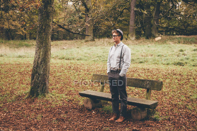 Young man standing in front of a bench in autumnal park looking at distance — Stock Photo