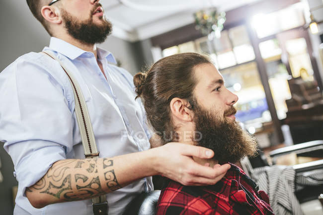 Man with full beard sitting with barber in barbershop — Stock Photo
