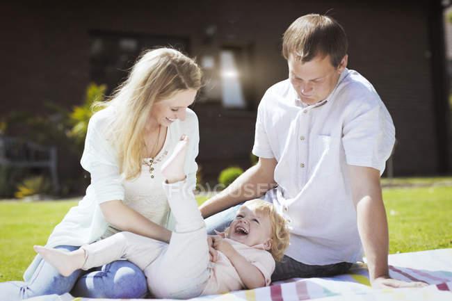 Parents jouant avec le petit fils sur la couverture dans le jardin — Photo de stock