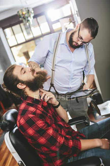 Barber with customer using digital tablet in barbershop — Stock Photo
