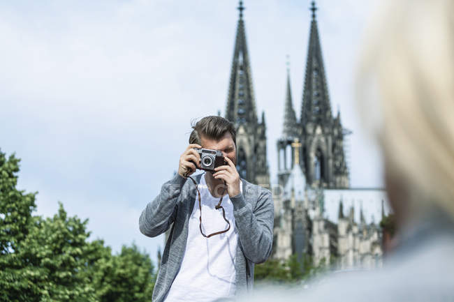 Germany, Cologne, man taking a picture of his girlfriend — Stock Photo