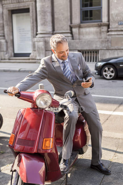 Smiling businessman sitting on motor scooter — Stock Photo