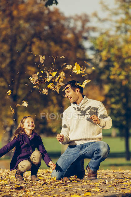 Portrait of happy father and daughter playing with dry leaves in a park — Stock Photo
