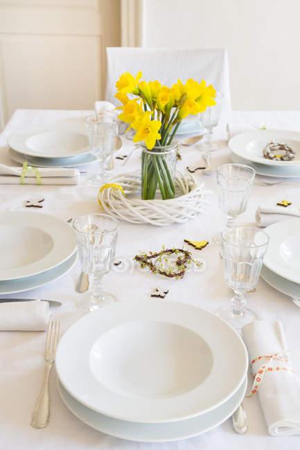 Gedeckter Tisch mit Narzissen im Frühjahr im Haus — Stockfoto