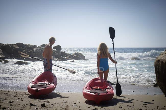 Couple de personnes âgées poussant les canots en bord de mer — Photo de stock
