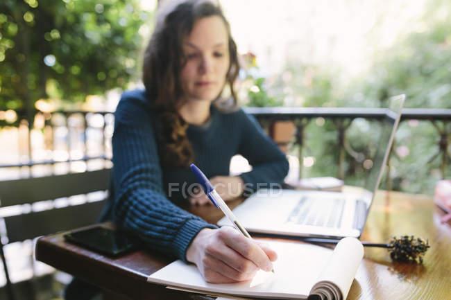 Молода жінка, сидячи на балконі, використовуючи ноутбук — стокове фото