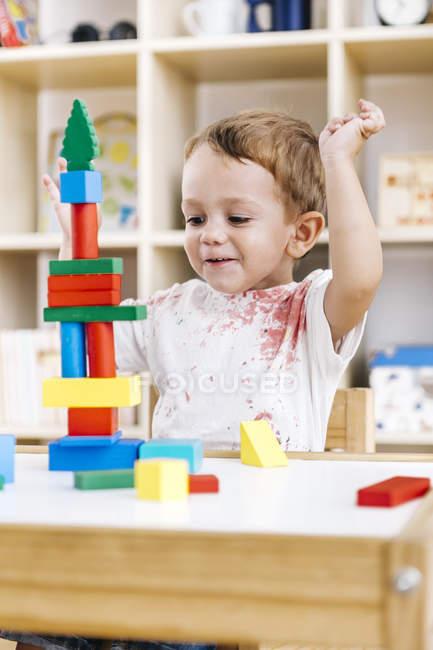 Portrait de petit garçon jouant avec des briques de construction — Photo de stock