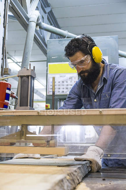 Craftsman with hearing protection, gloves and safety glasses using an industrial circular saw in a factory — Stock Photo