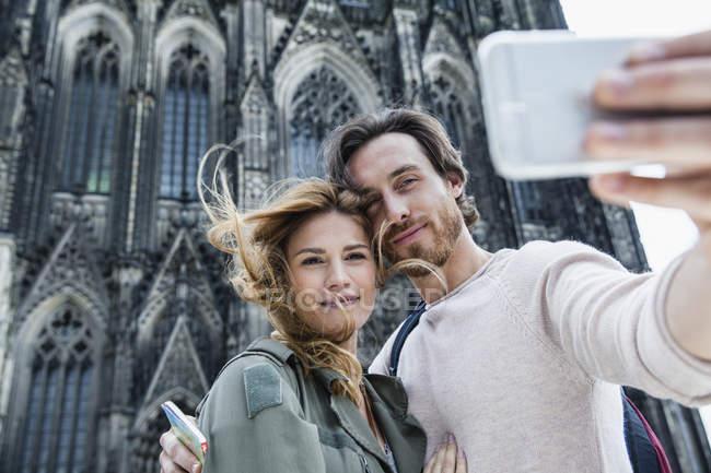 Retrato de Alemania, Colonia, de pareja de jóvenes teniendo una selfie frente a la Catedral de Colonia - foto de stock