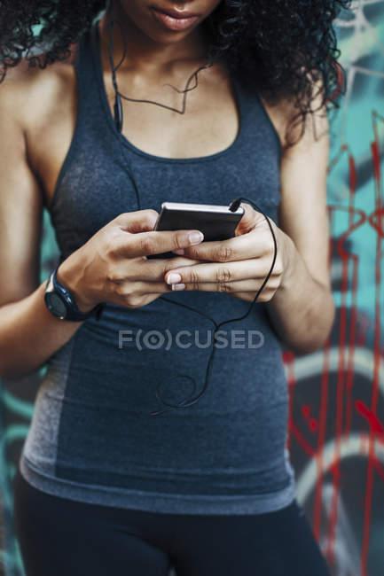 Mulher segurando smartphone com fones de ouvido — Fotografia de Stock