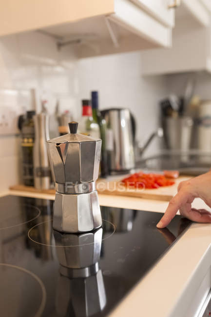 Еспресо можна на керамічній плитою скло, чоловічий пальця перемикання на плиті — стокове фото