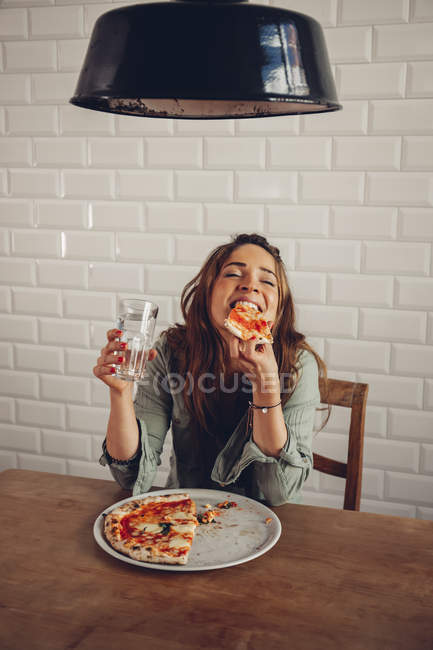 Young woman eating pizza in restaurant — Stock Photo