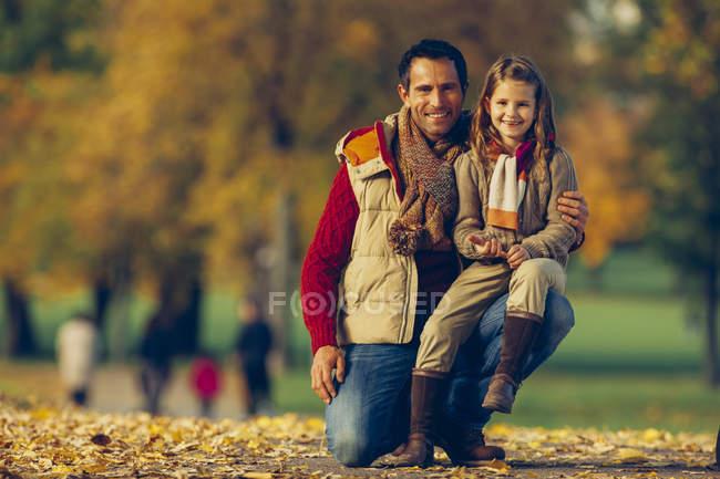 Портрет маленькой девочки с отцом в осеннем парке — стоковое фото