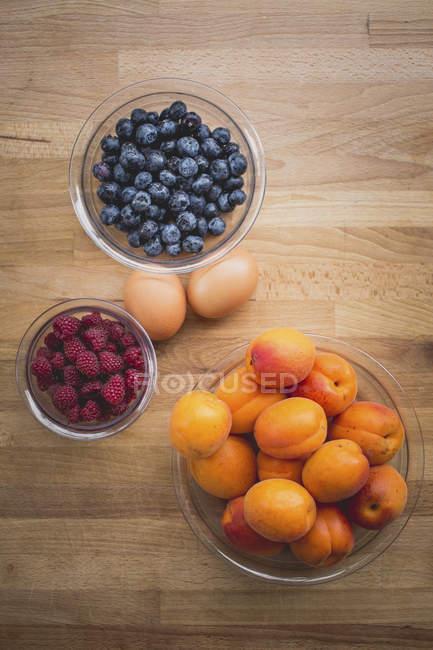 Стеклянные миски абрикосов, черники и малины с двумя коричневыми яйцами на дереве — стоковое фото