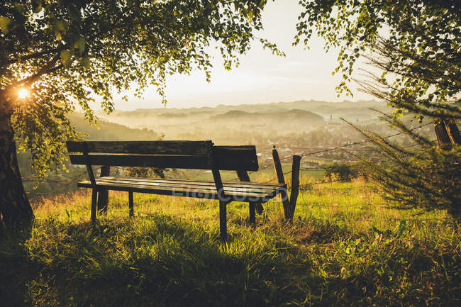 Austria, Styria, wine route, Bench and view to Schlossberg and Leutschach in summer against the sun — Stock Photo
