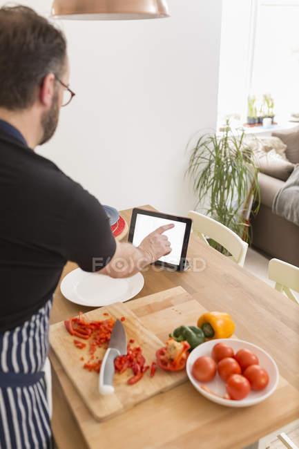 Homme utilisant une tablette numérique lors de la préparation des aliments dans la cuisine — Photo de stock