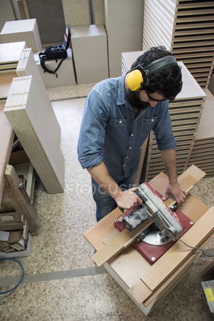 Carpenter with hearing protection and safety glasses using a circular saw — Stock Photo