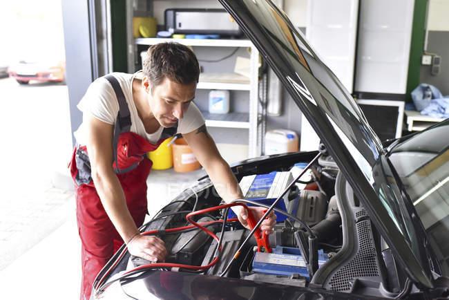 Meccanico di auto che lavora in garage di riparazione, ricarica batteria auto — Foto stock