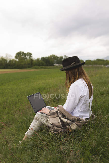 Жінка сидить на луг, використовуючи ноутбук — стокове фото