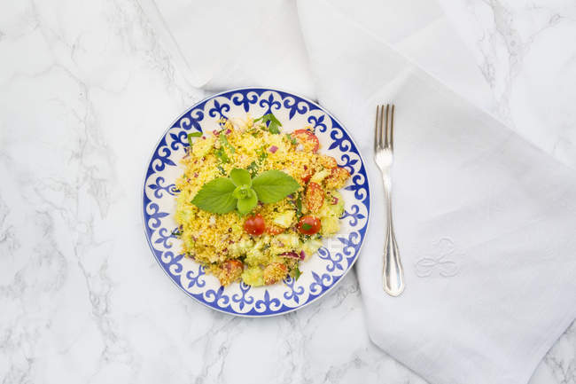 Plate of couscous salad, cloth and fork on white marble — Stock Photo