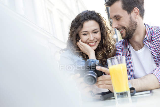 Young couple with camera having a rest in a pavement cafe — Stock Photo