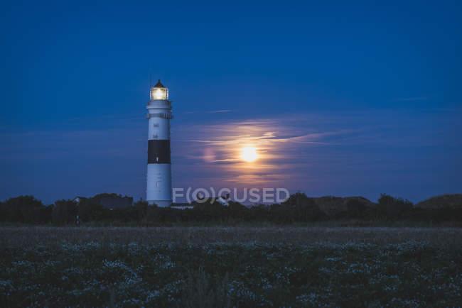 Illuminated lighthouse at moonlight — Stock Photo