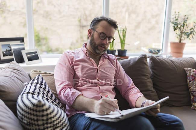 Älterer Mann sitzt auf Couch und markiert Werbung in Zeitung — Stockfoto