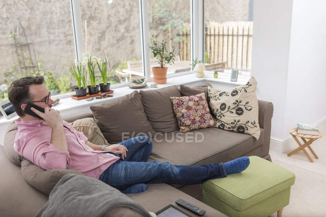 Зрелый мужчина сидит на диване и разговаривает по телефону. — стоковое фото