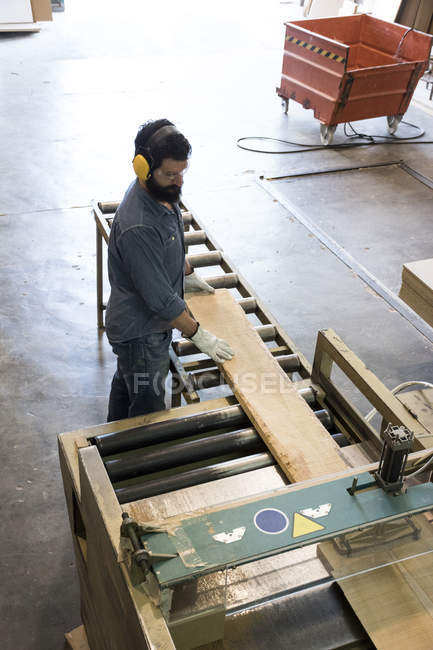 Man with gloves, hearing protection and safety glasses putting a wood plank on an industrial circular saw in a factory — Stock Photo
