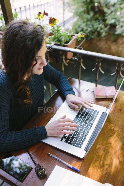 Young woman sitting on balcony using laptop — Stock Photo