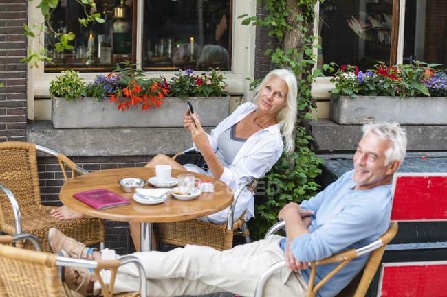 Pareja senior relajado, Países Bajos, Amsterdam, en un café al aire libre - foto de stock
