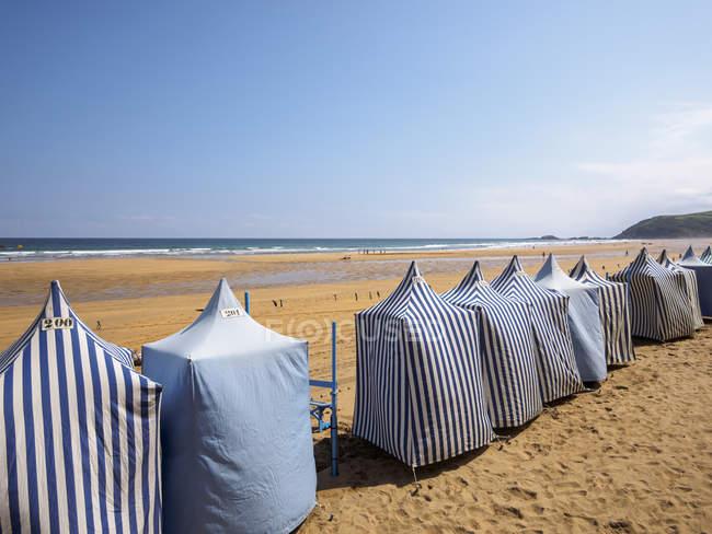 Испания, Зарауз, вид на пляж с рядами палаток против воды — стоковое фото