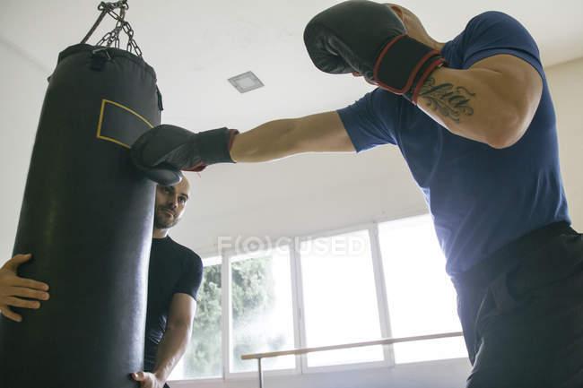 Boxer schlägt einen Boxsack, gehalten von einem Trainingspartner — Stockfoto