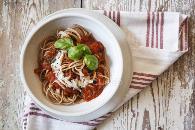 Schüssel mit Dinkel-Vollkornspaghetti, Tomatensauce, Parmesan und Basilikum — Stockfoto