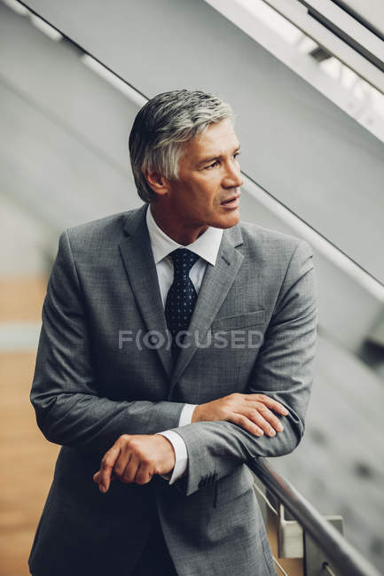 Mature businessman standing by railing looking away — Stock Photo