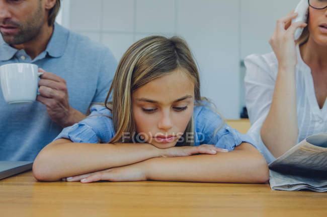 Разочарованная девушка, сидящая за столом с рассеянными родителями — стоковое фото