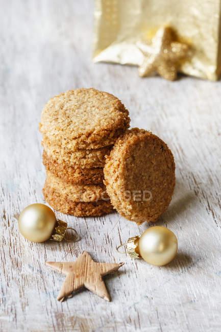 Pilha de biscoitos de cocos de grão inteiro e decoratiosn de Natal em madeira — Fotografia de Stock