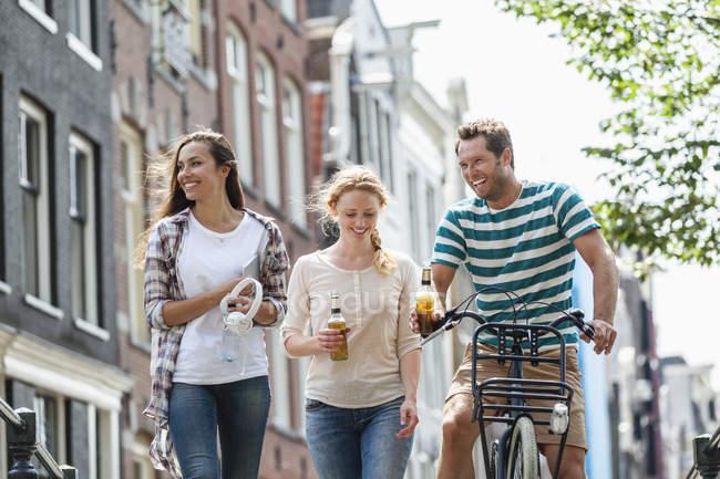 Paesi Bassi, Amsterdam, amici felici con bottiglie di birra e bicicletta in città — Foto stock