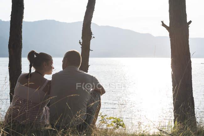 Болгарія, Родопи, пара сидять поруч на березі доспати водосховище — стокове фото