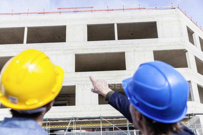 Двоє чоловіків на будівельному майданчику носити каски — стокове фото