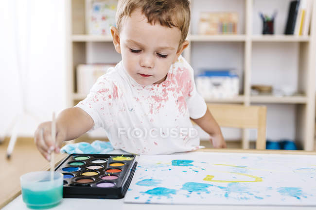 Portrait of little boy painting with watercolours — Stock Photo